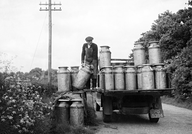 milk churns being loaded onto a lorry at a farm